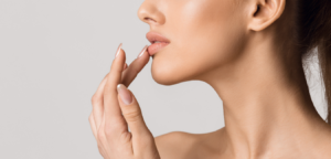 twarz kobiety, która dotyka palcem swoich pełnych, miękkich ust